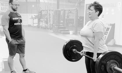 Woman lifting weights while Coach watches